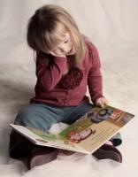 """Down-szindrómás kislány ölében képeskönyvvel az """"alszik"""" babajelet mutatja"""
